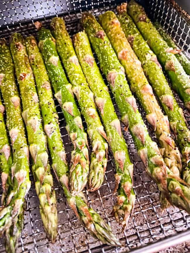 Asparagus stalks coming out of an air fryer machine in a basket