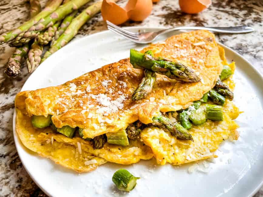 Asparagus Omelette topped with vegetables on a white plate