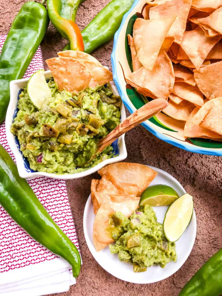 A spread of Hatch Green Chile Guacamole in a bowl with chips and a plate being served up