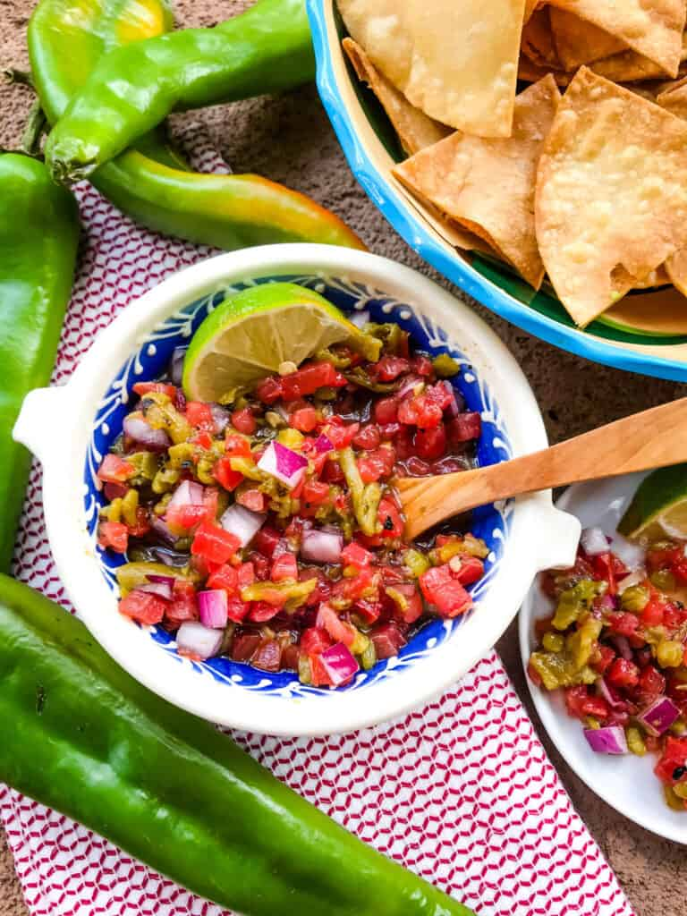 A bowl of the salsa with a wooden spoon