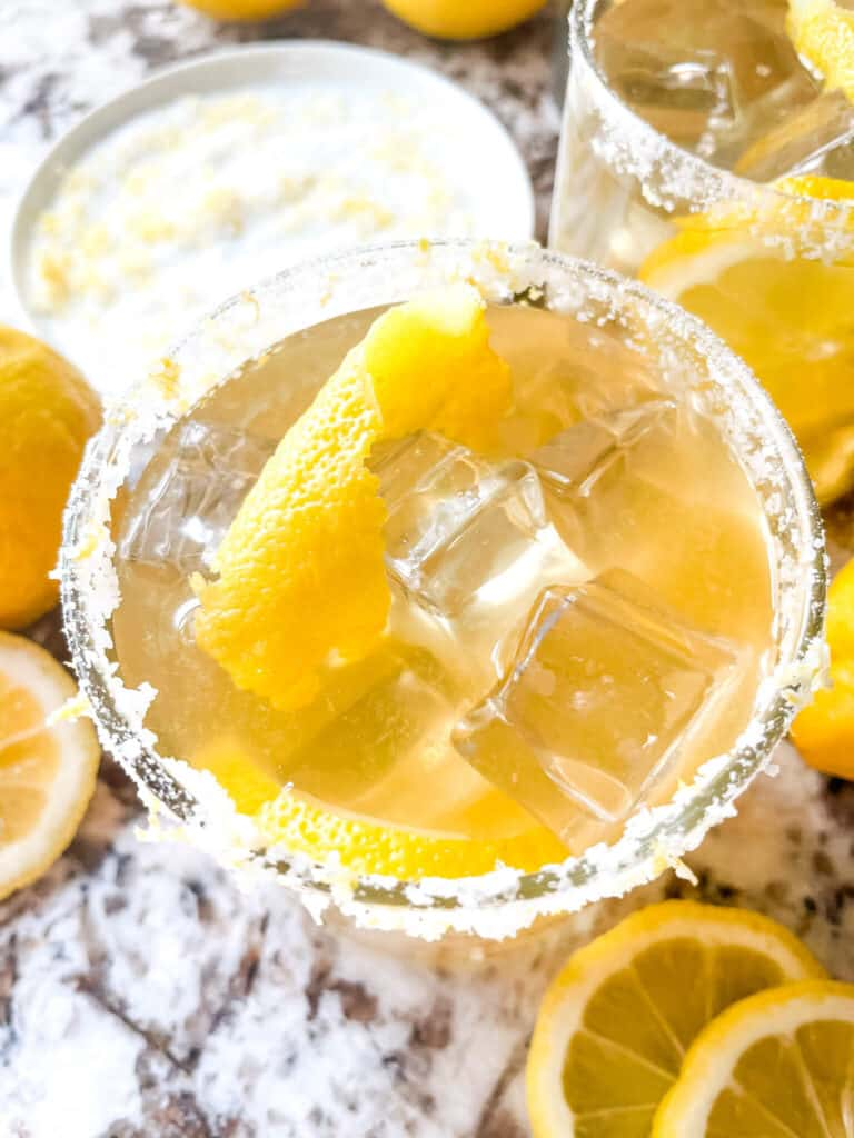 Top view of a glass of Lemon Margarita with a salt rim and lemon peel in it