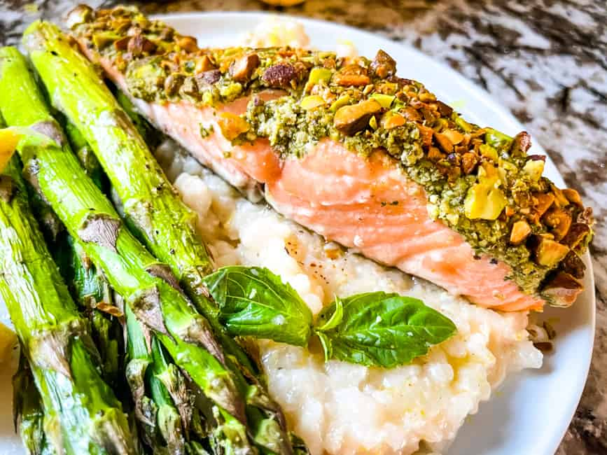Pesto Crusted Salmon on a bed of Risotto al limone with air fryer asparagus on a plate
