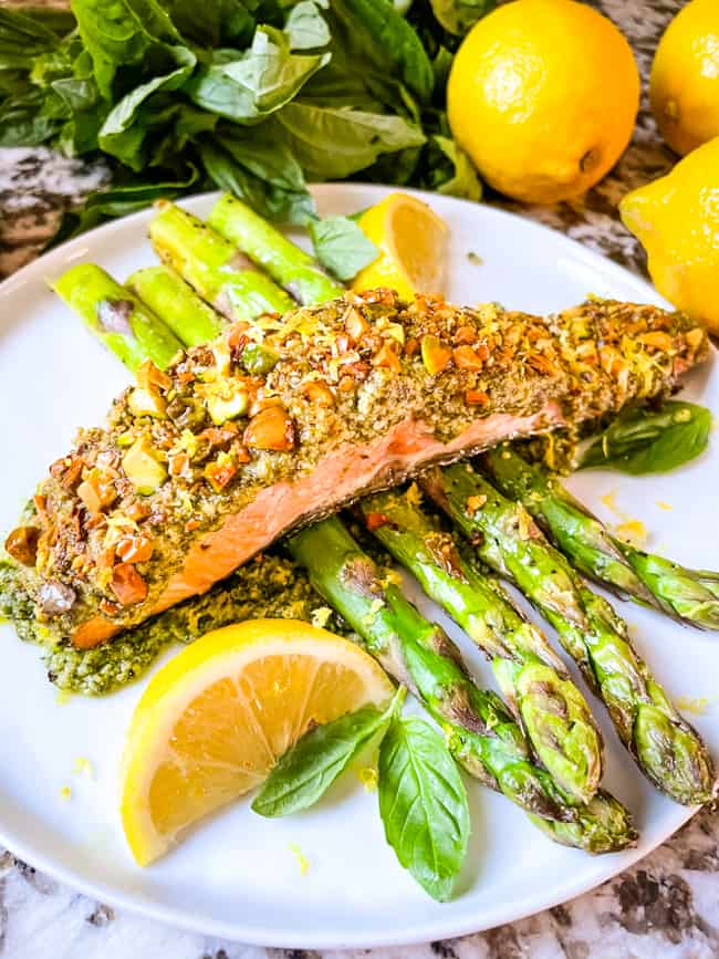 Crusted fish on a bed of air fryer asparagus on a white plate with lemons