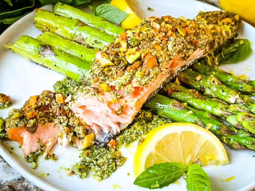 Pesto Crusted Salmon partially eaten on top of asparagus