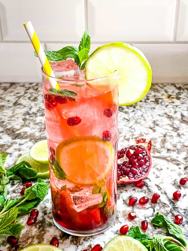 One tall glass of Pomegranate Mojito with limes and pomegranate seeds