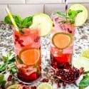 Two glasses of Pomegranate Mojito surrounded by pomegranates and limes