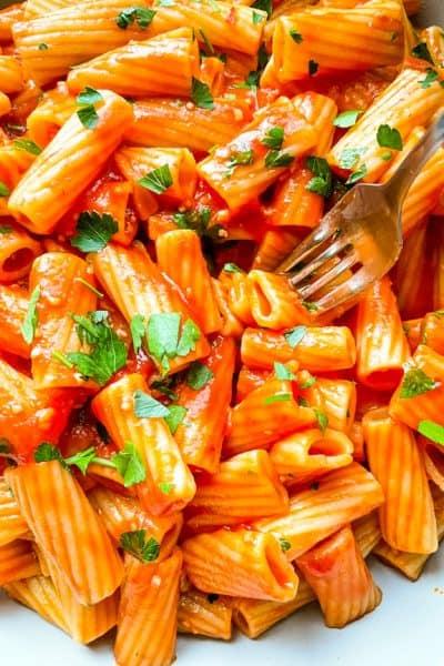 A fork digging into a large bowl of Rigatoni Arrabbiata
