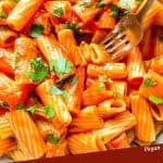 Pin image of a fork digging into Rigatoni Arrabbiata with title at bottom