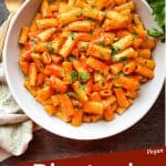Pin image of a bowl of Rigatoni Arrabbiata on a towel with title at bottom