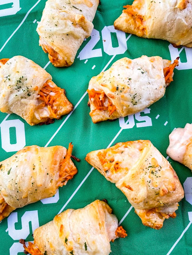 Buffalo Chicken Crescent Rolls scattered on a football field tablecloth