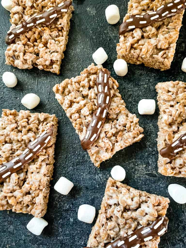 Serveral cereal bars on a black board with marshmallows