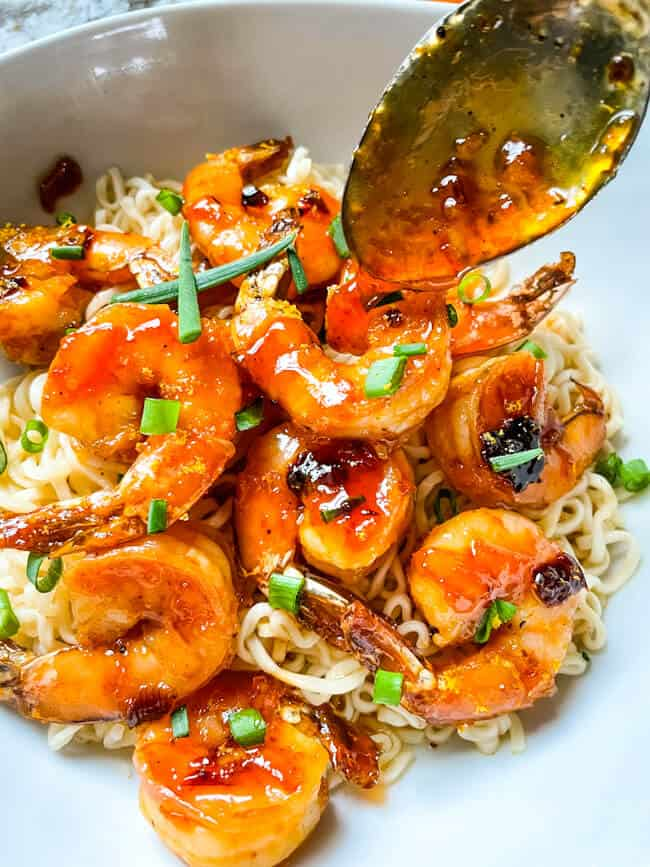 A spoon pouring sauce over Chipotle Orange Glazed Shrimp on top of noodles