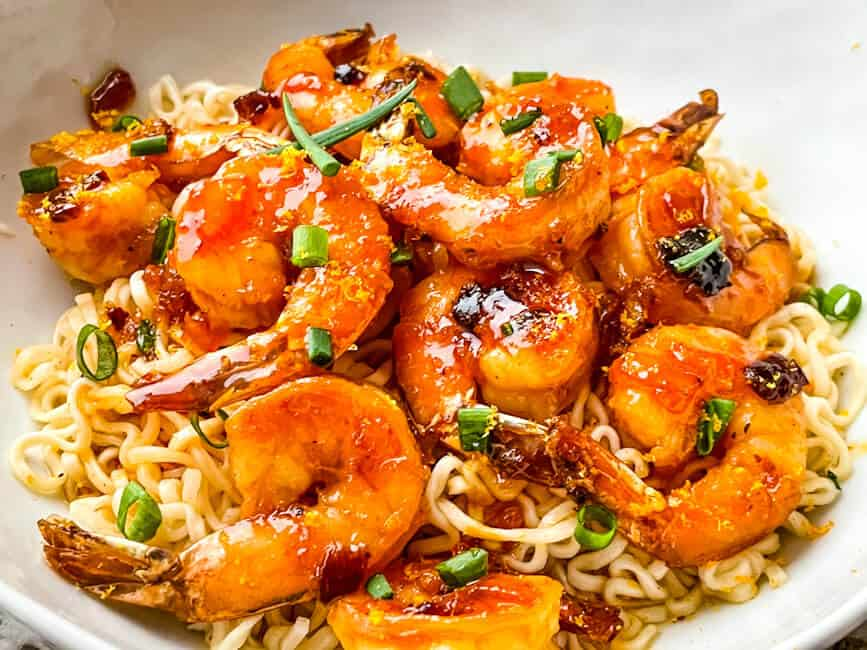 A pile of Chipotle Orange Glazed Shrimp on a bed of noodles in a bowl
