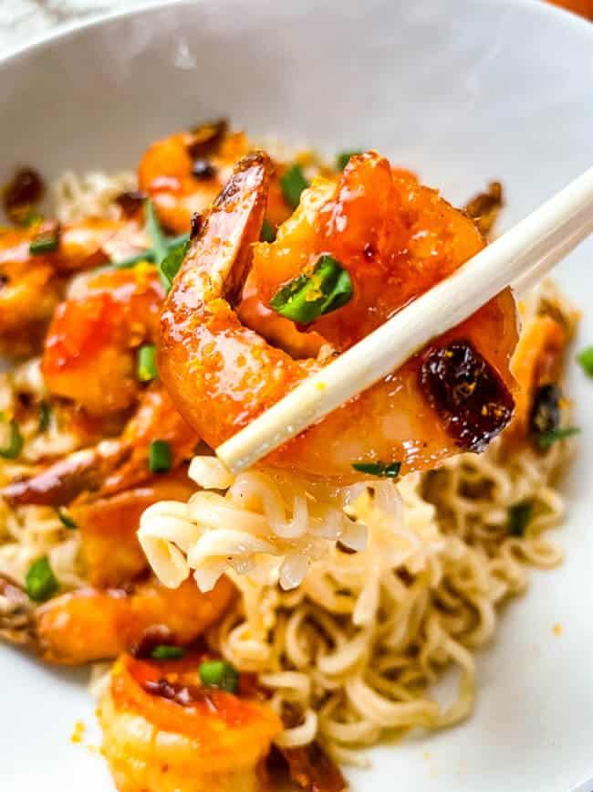 Chopsticks holding a shrimp over a bowl of the food