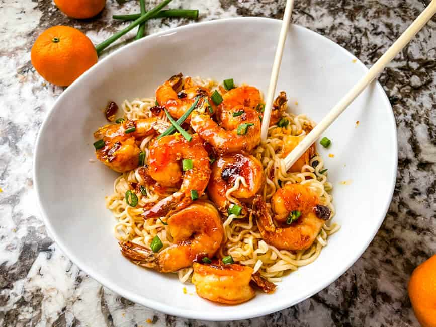 A white bowl with noodles and the seafood. Chopsticks sticking out of the bowl