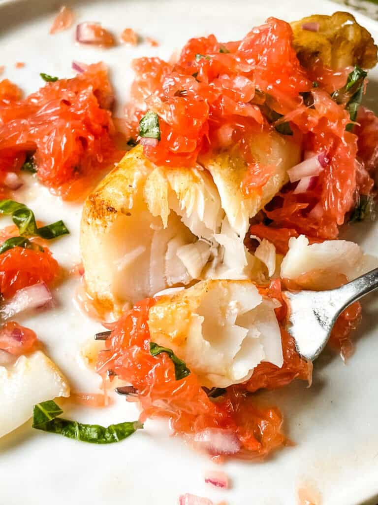 A fork digging into Cod with Grapefruit Relish