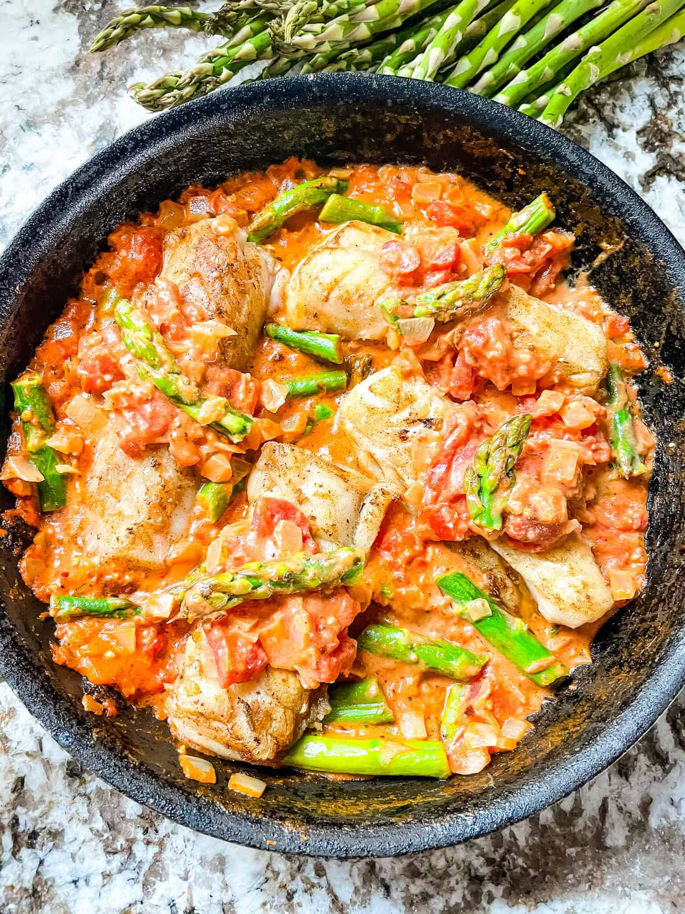 The fish cooked in the sauce in a skillet