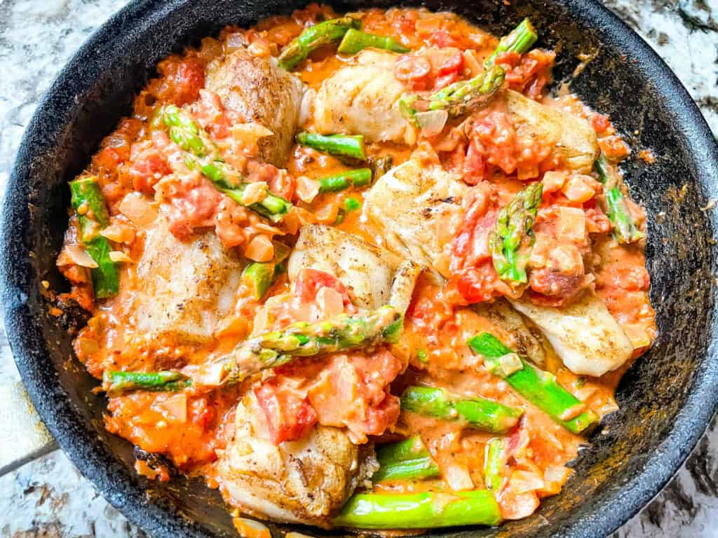 Top view of Cod Pomodoro with Asparagus in a skillet
