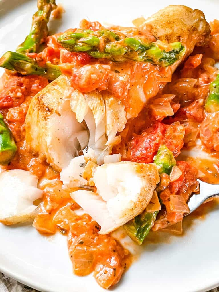A Cod Pomodoro with Asparagus with a fork having dug into the flaky fish