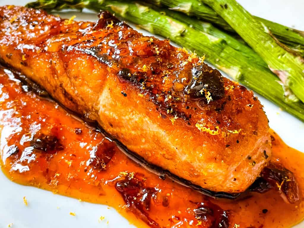 A piece of fish with the sauce and asparagus on a white plate