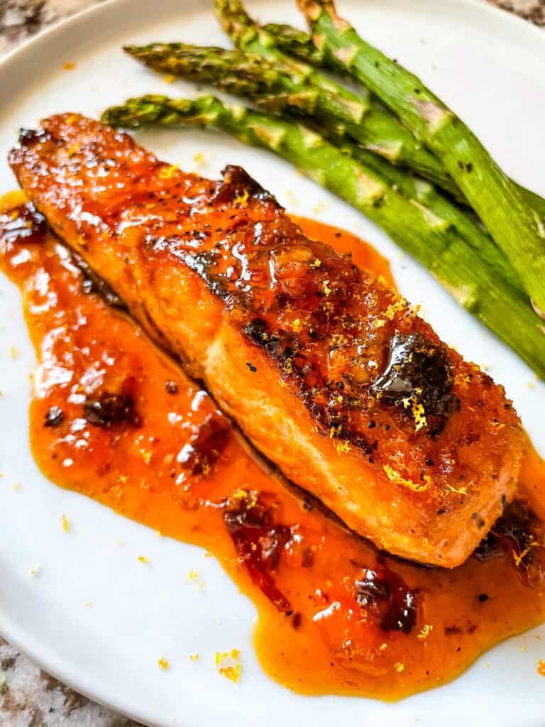 A full Chipotle Orange Glazed Salmon steak with sauce on a white plate with asparagus