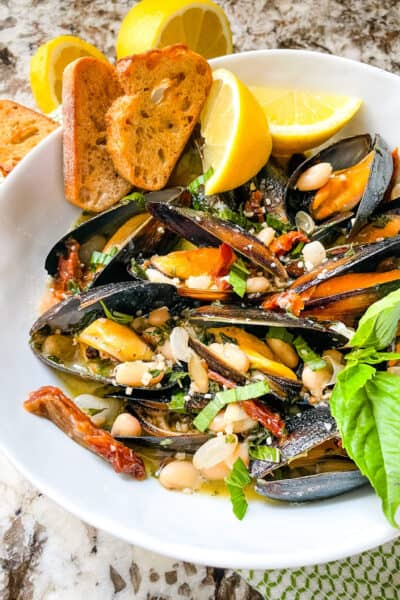 Copycat Maggiano's Tuscan Mussels in a white bowl with lemons and bread
