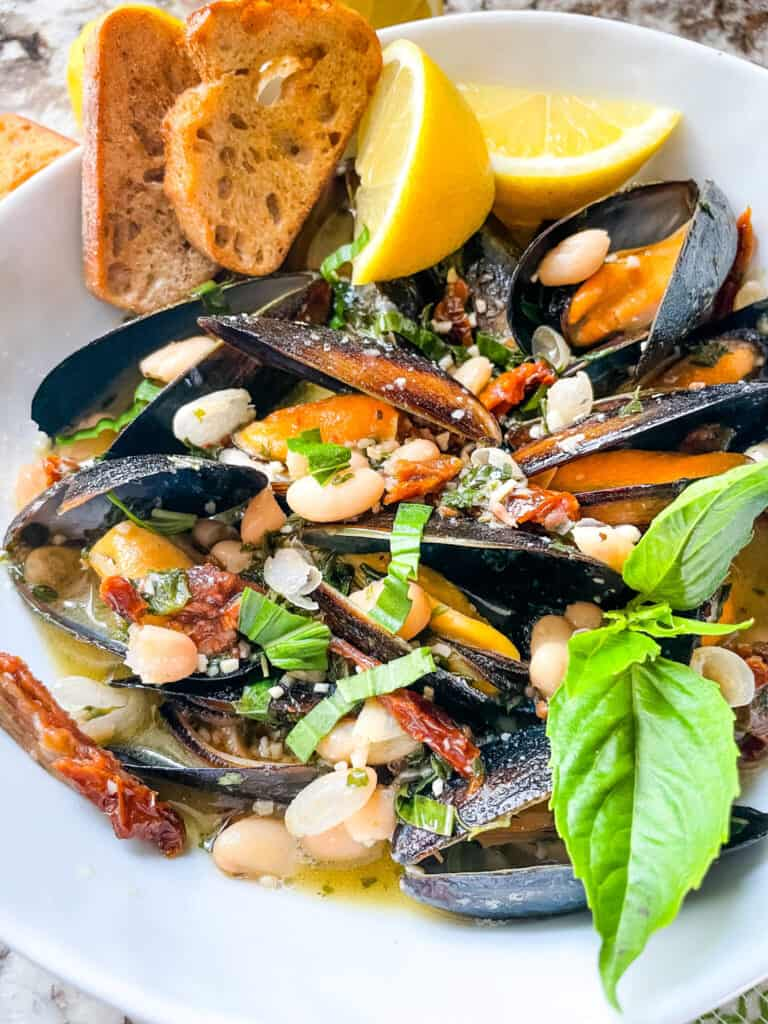 The shellfish and sauce in a bowl with basil