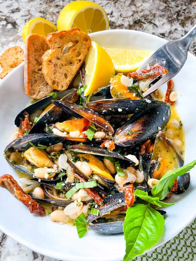 A fork digging into a bowl of Copycat Maggiano's Tuscan Mussels