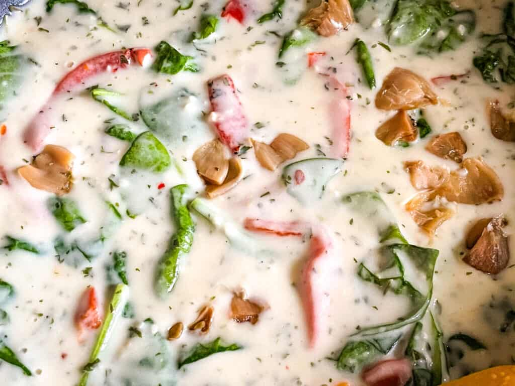 The creamy sauce with vegetables being cooked