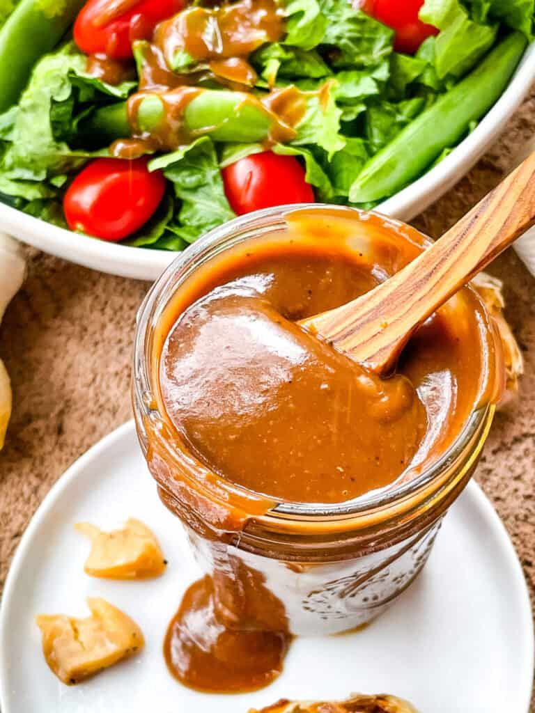 A jar of Creamy Balsamic Dressing with a wood spoon sticking out