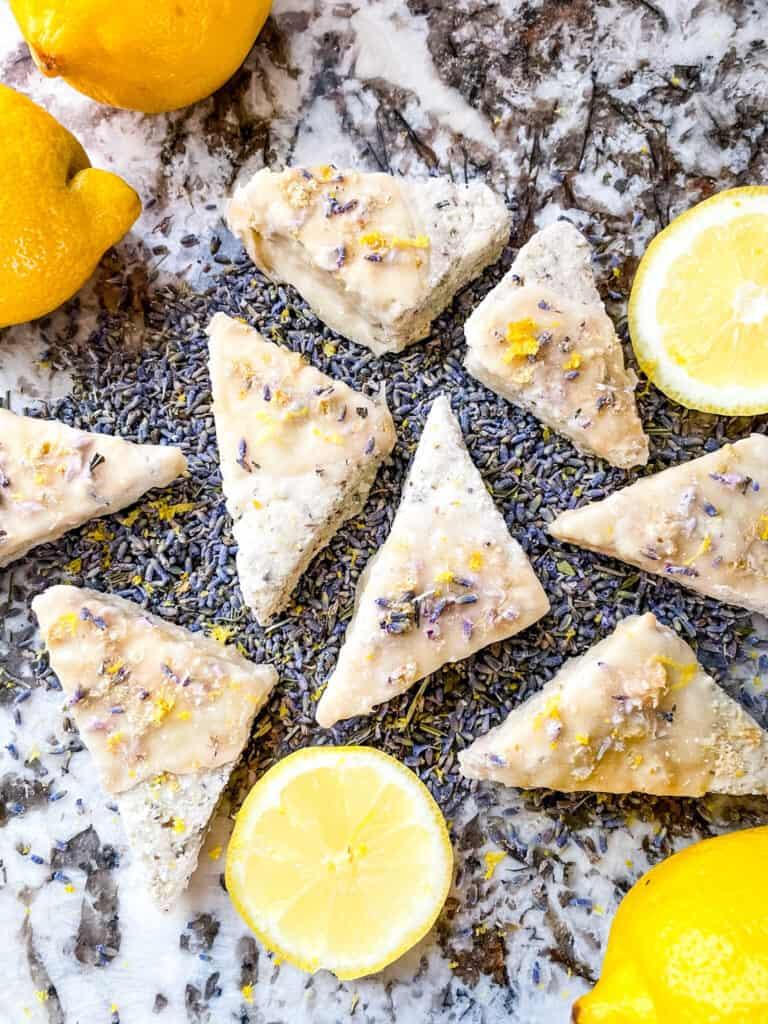 Lemon Lavender Shortbread Cookies scattered across lavender buds with lemon pieces