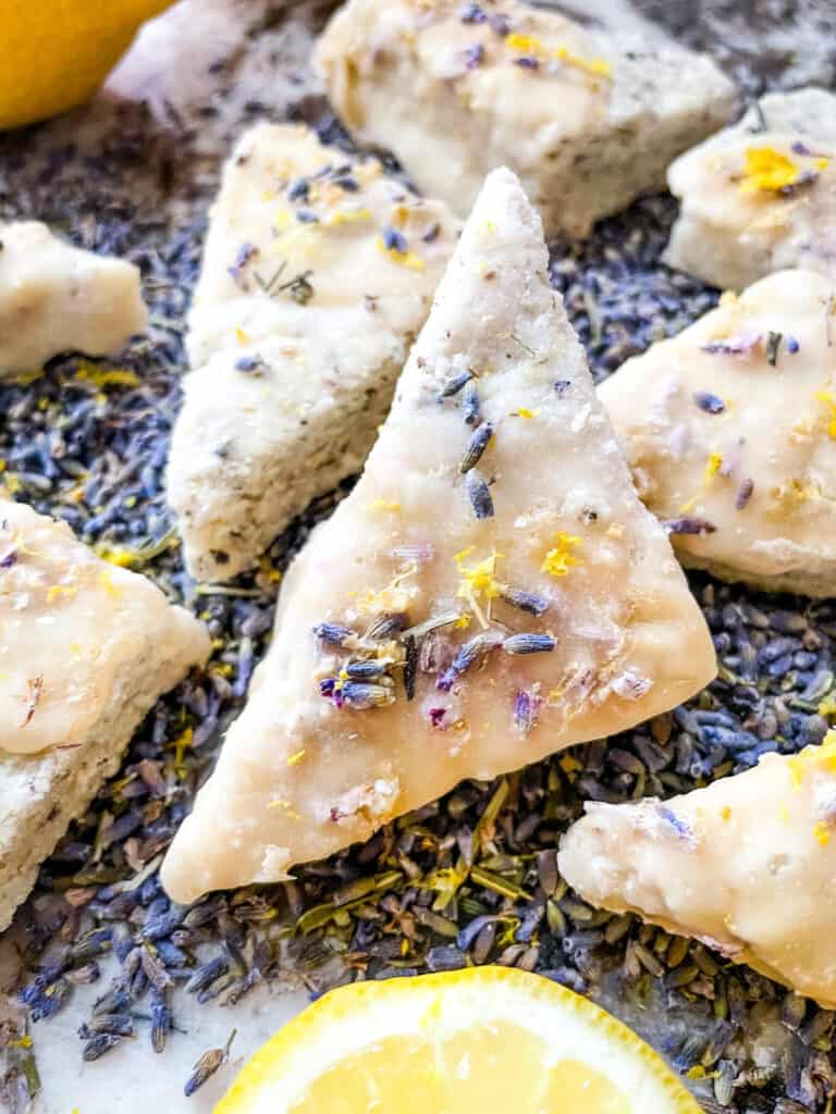 A close up of a triangular lavender cookie on top of flowers