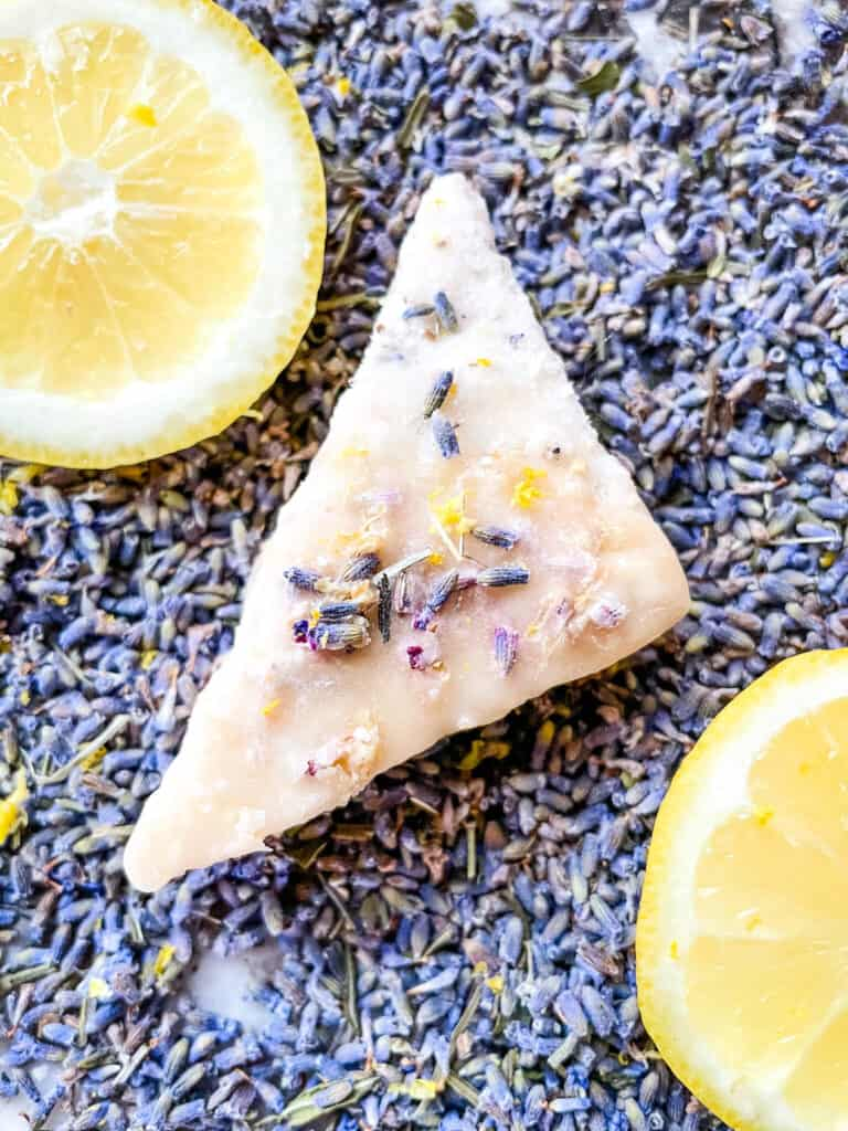 A lavender cookie on top of lavender buds with lemon slices