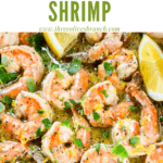 Pin image of Lemon Pepper Shrimp in a skillet with lemon wedges and title at top
