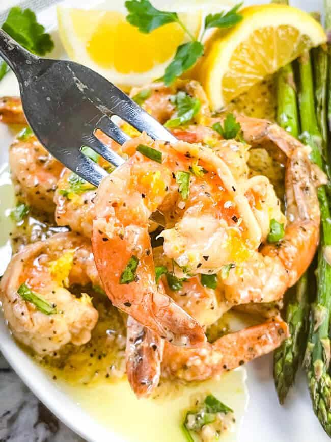A fork holding a Lemon Pepper Shrimp above the plate