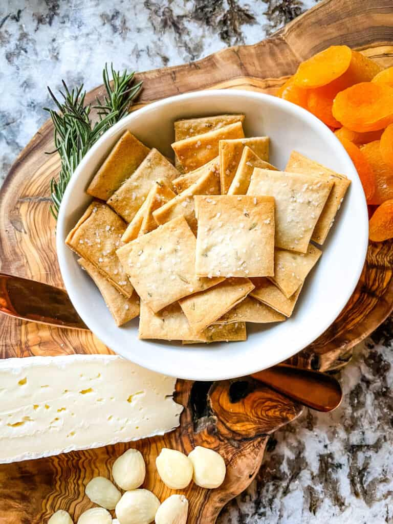 A white bowl full of Rosemary Sourdough Crackers on a charcuterie board