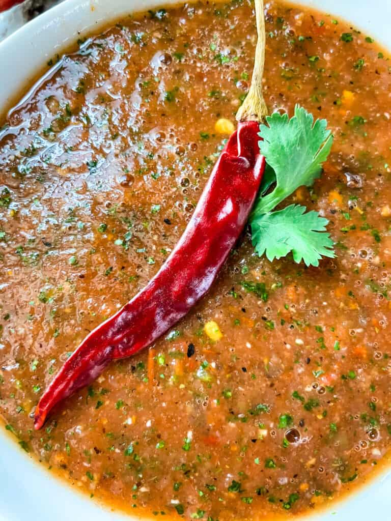 Close up of Salsa Chile de Arbol with a pepper on top