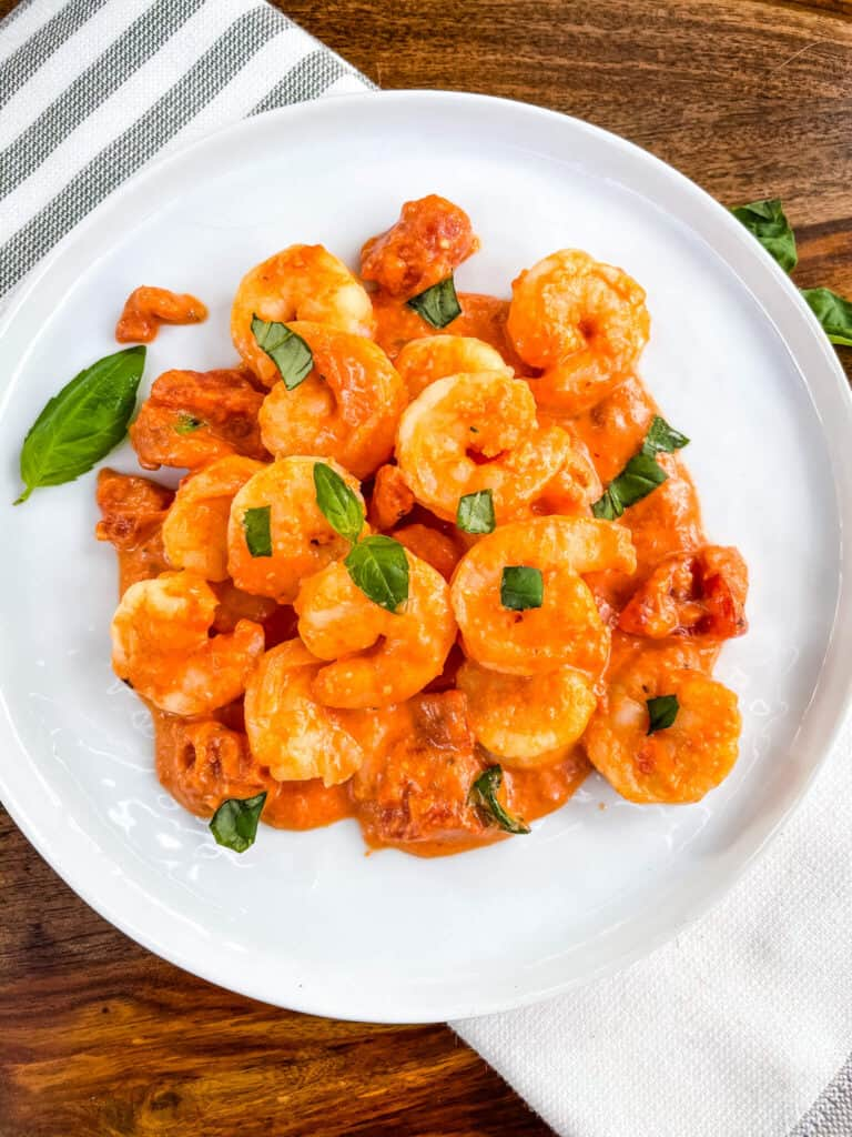 Top view of a pile of Shrimp in Vodka Sauce on a white plate with pieces of fresh basil