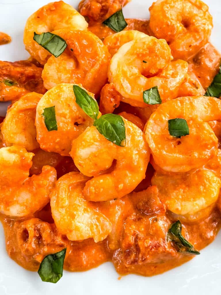 Close view of Shrimp in Vodka Sauce in a pile on a white plate