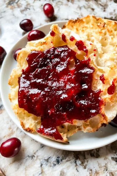 Cranberry Jam on an English muffin on a plate with some berries around it