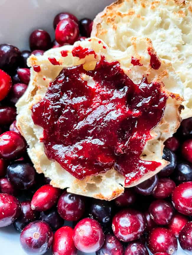Cranberry Jam on an English muffin sitting in a bowl full of fresh cranberries