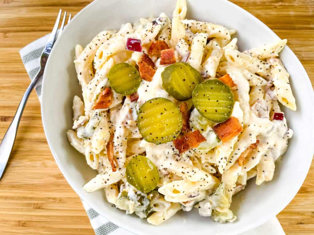 A white bowl filled with the creamy side dish and pickles on top