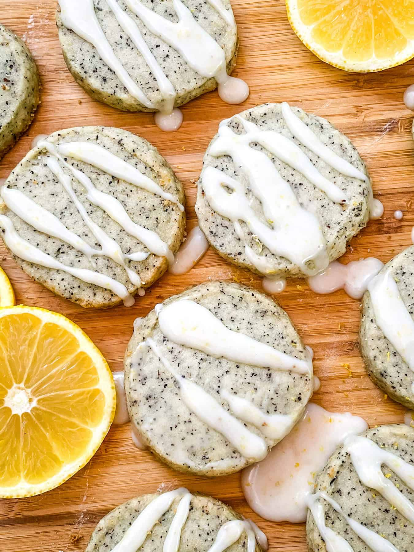 Earl Grey Shortbread Cookies spread out on a cutting board with drizzled glaze and lemon slices