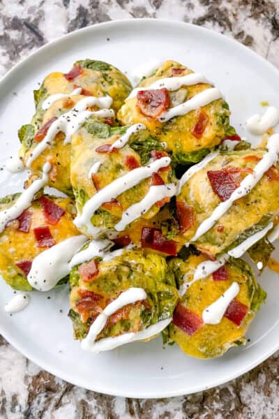A pile of Loaded Smashed Brussels Sprouts drizzled with sour cream on a white plate