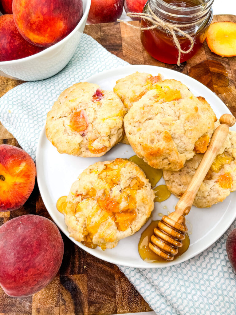 Peach Scones on a white plate with a honey wand