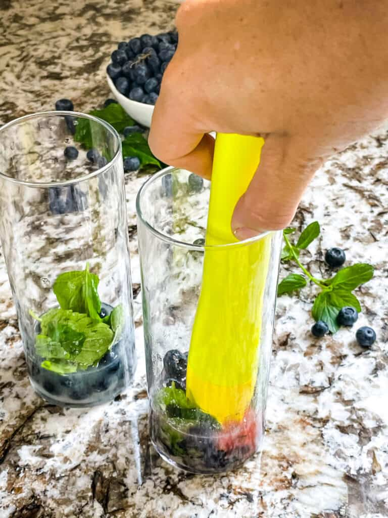 A hand muddling ingredients in a tall glass