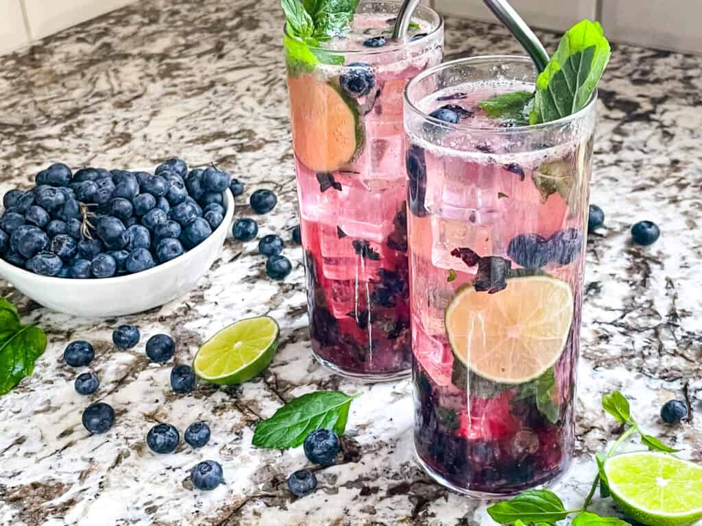 Two Blueberry Mojitos with berries around them