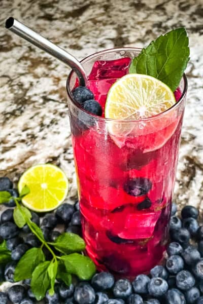 A bright pink Blueberry Mojito after being stirred