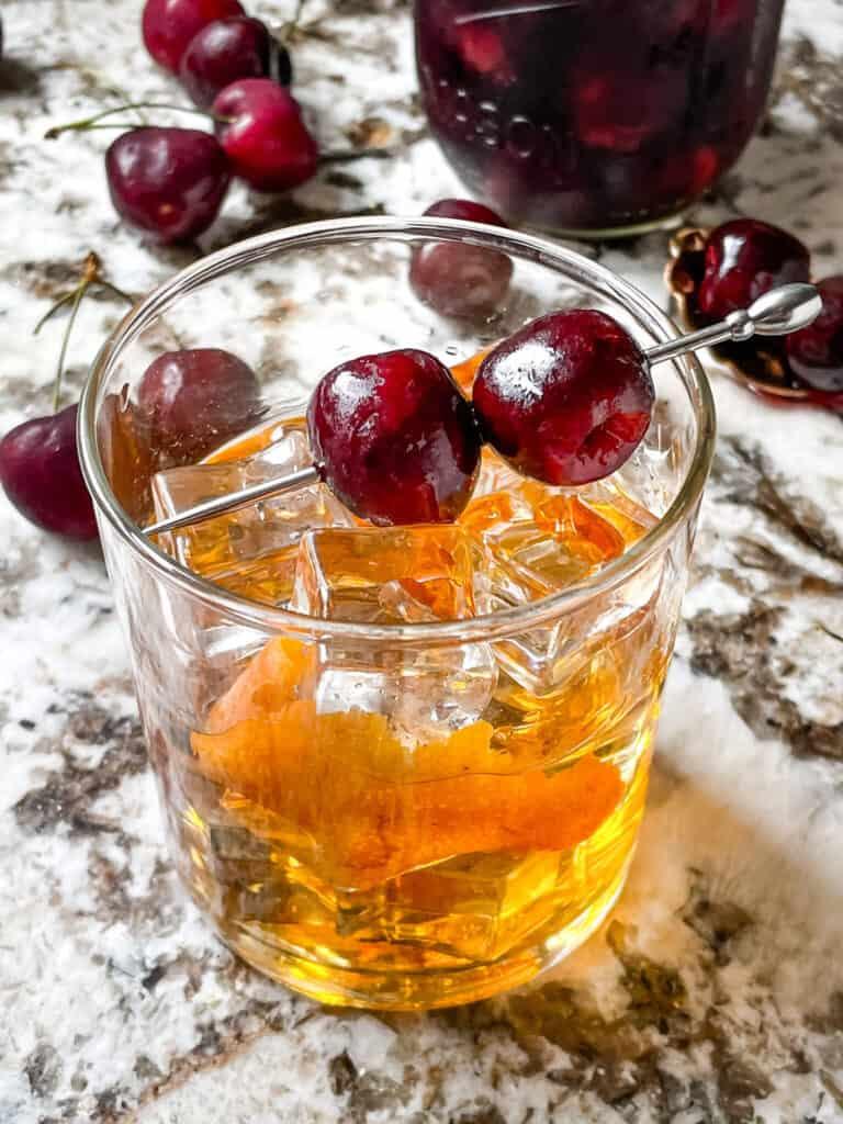 A skewer of Brandied Cherries on top of a cocktail
