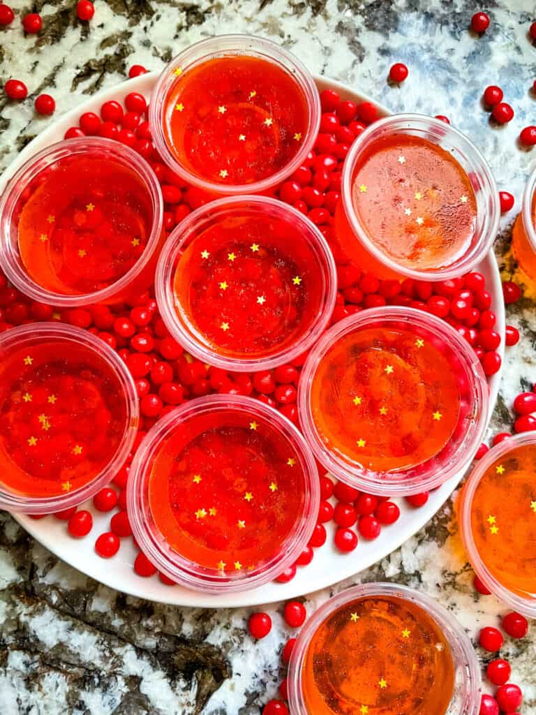 A round plate filled with little cinnamon candies and the shot cups on top, from top view